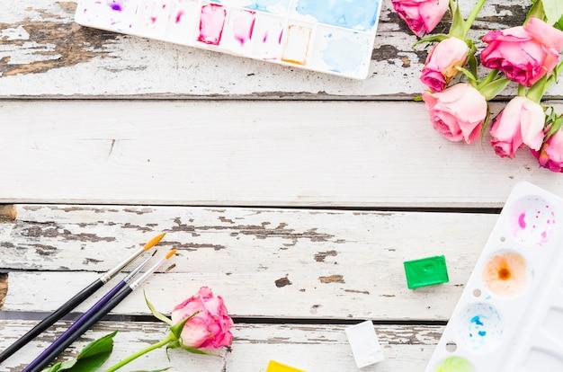 Vue de dessus des fleurs avec du matériel de peinture sur une table en bois