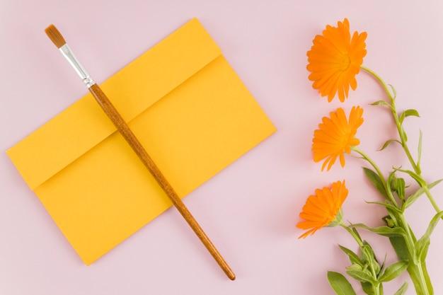 Vue de dessus des fleurs avec enveloppe et pinceau