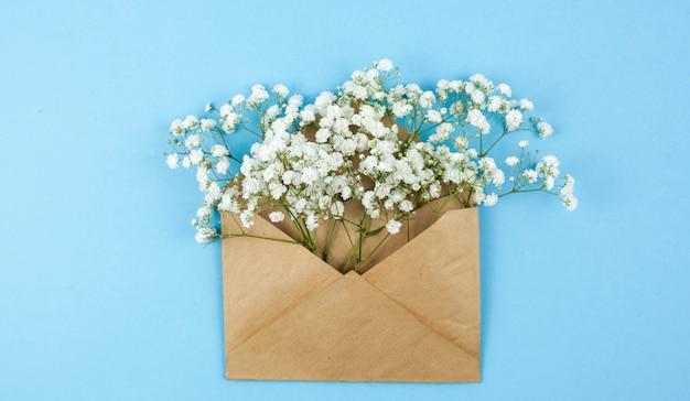 Vue de dessus des fleurs d'haleine de bébé sur une enveloppe brune