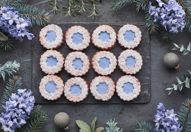 Vue de dessus des fleurs linzer cookies avec vitrage bleu sur fond sombre d'hiver avec des herbes et des fleurs