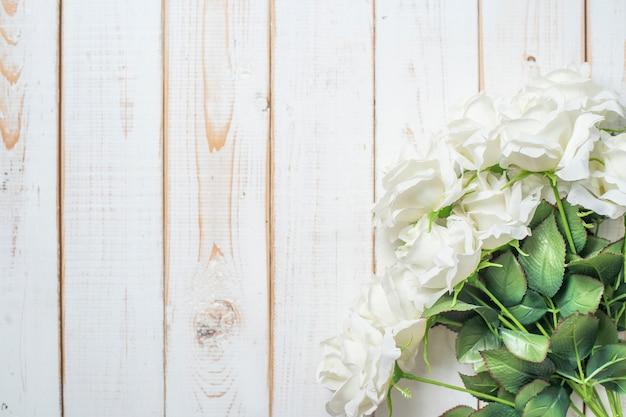 Vue de dessus des fleurs de mariage sur fond de bois blanc