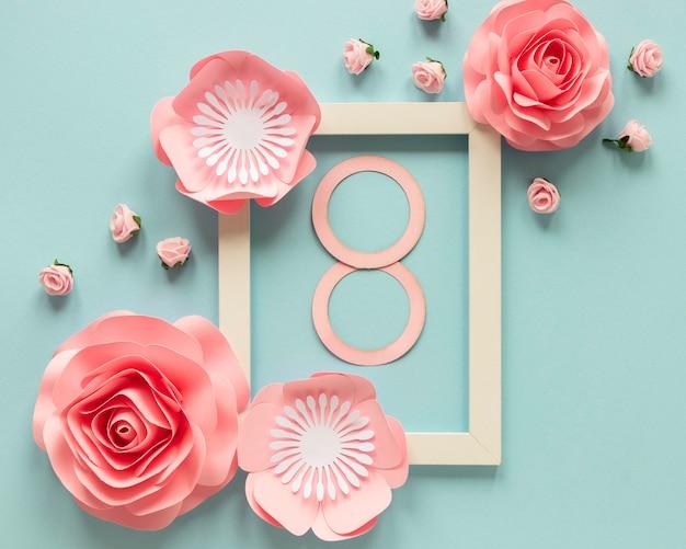 Vue de dessus des fleurs en papier avec cadre et date pour la journée de la femme