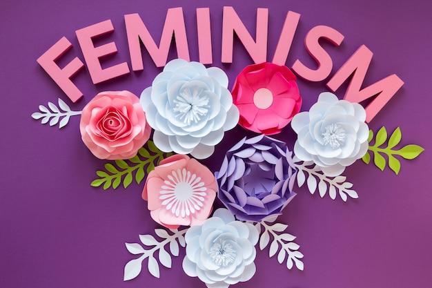 Vue de dessus des fleurs en papier avec le mot féminisme pour la journée de la femme