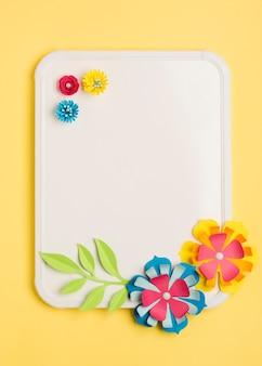 Vue de dessus des fleurs en papier pour le printemps et le tableau blanc