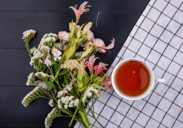 Vue de dessus des fleurs rose clair avec une tasse de thé sur une serviette à carreaux blancs sur une surface noire