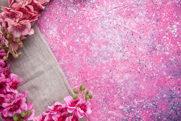 Vue de dessus des fleurs roses sur la surface rose concept printemps couleur ornée de vacances de pâques coloré