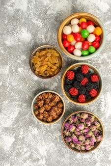 Vue de dessus des fleurs séchées avec des bonbons et des confitures de baies sur une surface blanche biscuit bonbon thé sucre biscuit sucré