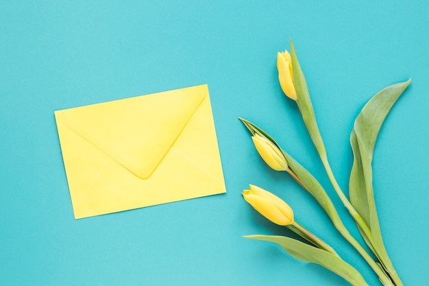 Vue de dessus des fleurs de tulipe jaune et enveloppe fermée