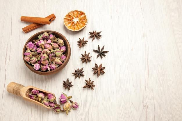 Vue de dessus des fleurs violettes à la cannelle sur un bureau blanc, saveur de fleur de couleur sèche