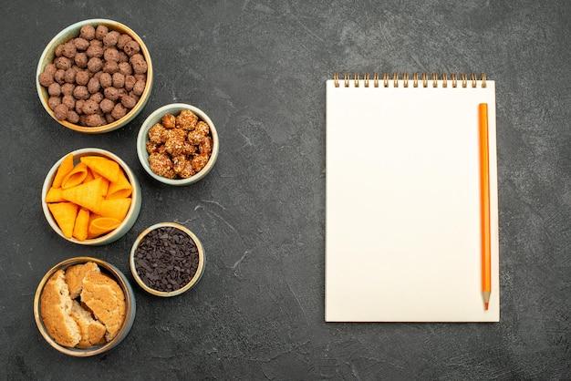 Vue de dessus des flocons de chocolat avec des chips sur un écrou de collation de couleur de fond gris foncé