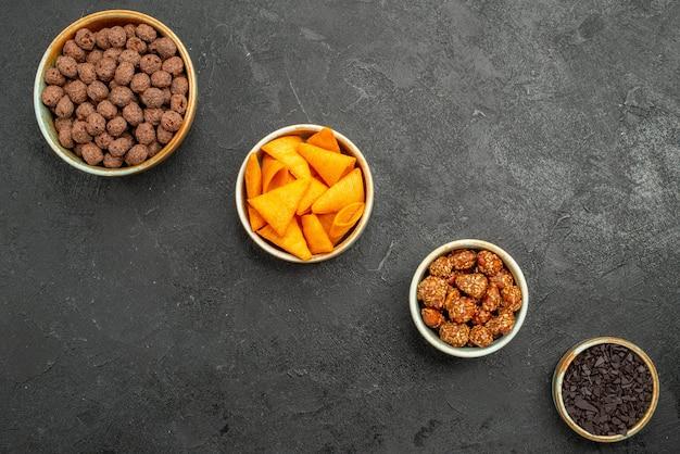 Vue de dessus des flocons de chocolat avec des noix sur fond sombre de nombreuses couleurs de flocons