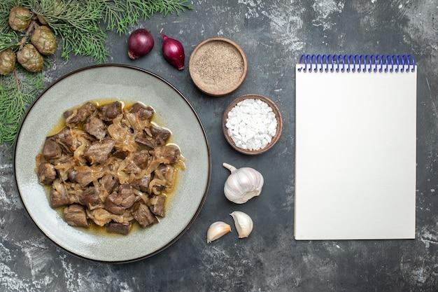 Vue de dessus foie et oignon cuits sur une assiette branche de pin sel de mer et poivre ail et cahier vide