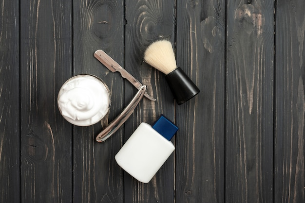 Vue de dessus, sur un fond en bois foncé outils de rasage: baume après rasage, rasoir, brosse à raser et crème à raser
