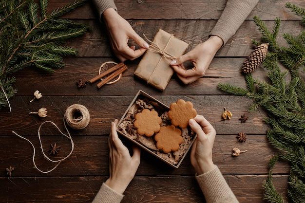 Vue de dessus fond de noël avec deux jeunes femmes méconnaissables emballant des biscuits faits maison en cadeau avec ...