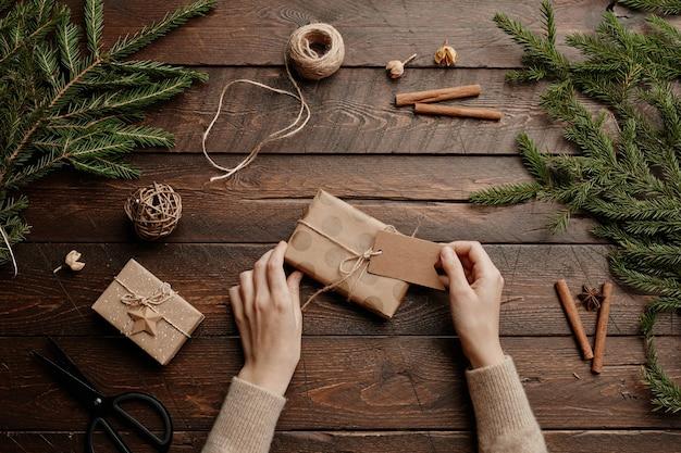 Vue de dessus de fond de noël avec une jeune femme enveloppant des cadeaux à une table en bois se bouchent