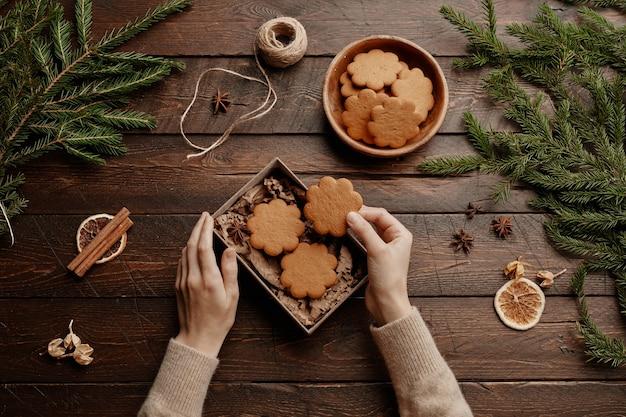 Vue de dessus fond de noël avec une jeune femme méconnaissable emballant des biscuits faits maison dans un emballage cadeau ...