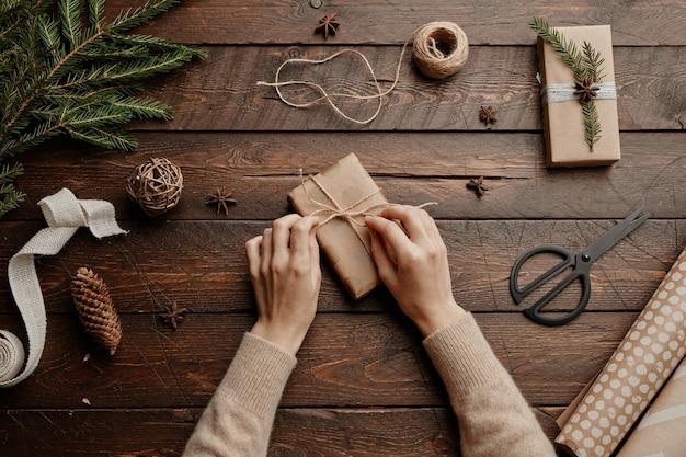 Vue de dessus fond de noël avec une jeune femme méconnaissable emballant des cadeaux à l'espace de copie de table en bois