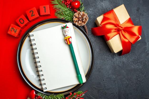 Vue de dessus de fond de nouvel an avec cahier à spirale sur assiette à dîner accessoires de décoration branches de sapin et numéros sur une serviette rouge et cadeau avec ruban rouge sur un tableau noir