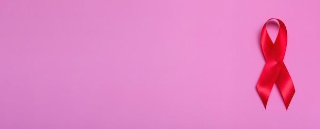 Vue de dessus sur fond rose avec concept de ruban rouge gros plan de la journée internationale du sida du 1er décembre. bannière