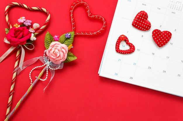 Vue de dessus le fond de la saint-valentin et les décorations. la marque de la broche rouge le 14 février au calendrier et le cadeau du bouquet de forme d'amour sur fond rouge et forme de coeur avec copie.