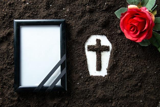 Vue de dessus de la forme de cercueil avec cadre photo et fleur rouge