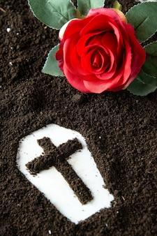 Vue de dessus en forme de cercueil avec sol brun et fleur rouge