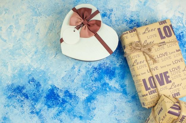 Vue de dessus en forme de coeur boîte cadeau spirale sur fond bleu avec espace libre