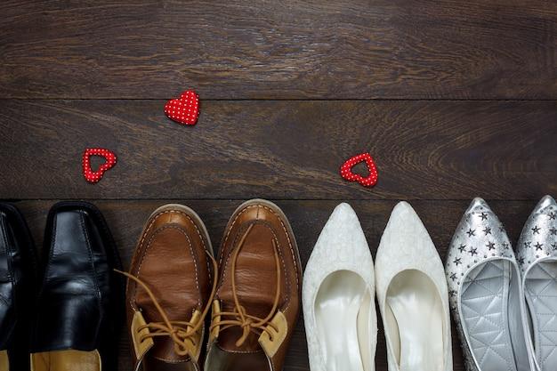 Vue de dessus en forme de cœur rouge avec plusieurs chaussures pour hommes et chaussures pour femmes sur fond en bois avec copie.