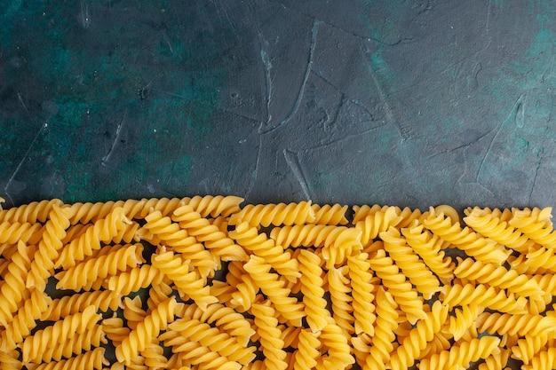 Vue de dessus en forme de pâtes italiennes sur un bureau bleu foncé
