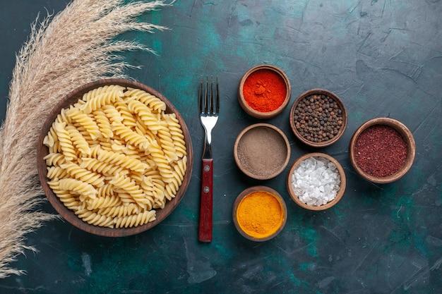 Vue de dessus en forme de pâtes italiennes avec différents assaisonnements sur fond bleu foncé
