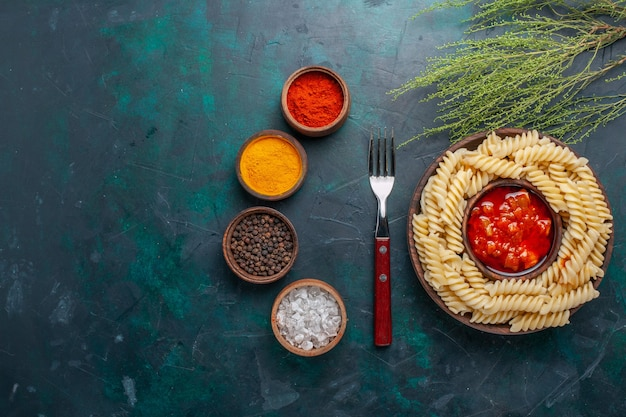 Vue de dessus en forme de pâtes italiennes avec sauce tomate et assaisonnements sur bureau bleu foncé
