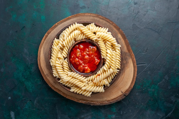 Vue de dessus en forme de pâtes italiennes avec sauce tomate sur fond bleu foncé