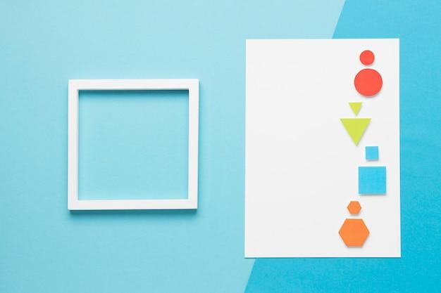 Vue de dessus des formes géométriques colorées à côté du cadre vide
