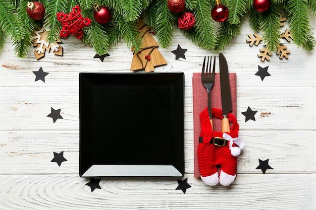 Vue de dessus de fourchette, couteau et assiette entourée de sapin et decoratoins de noël sur bois.