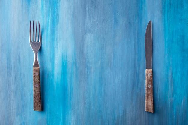 Vue de dessus avec une fourchette et un couteau sur fond bleu. espace texte.