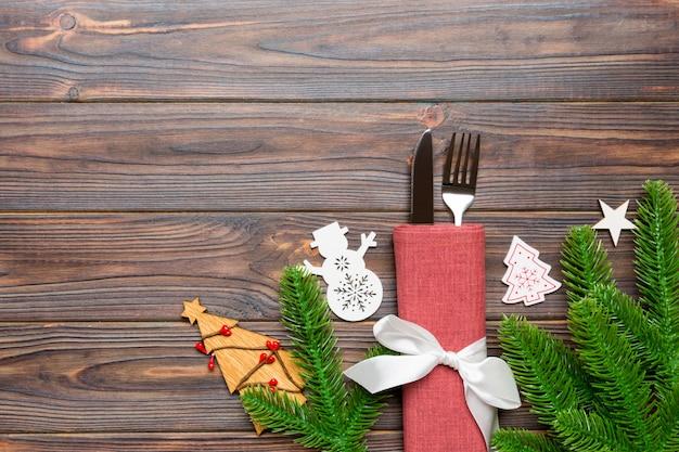 Vue de dessus de fourchette et couteau sur la serviette avec des décorations de noël et nouvel an des arbres sur fond en bois. vacances et fête avec fond