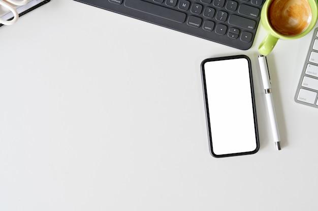Vue de dessus des fournitures de bureau d'espace de travail. téléphone mobile à écran blanc et espace de copie