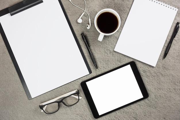 Une vue de dessus des fournitures de bureau avec une tasse de café et une tablette numérique sur un bureau gris