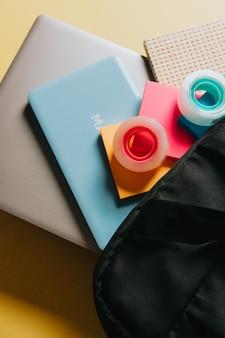 Vue de dessus des fournitures de papeterie noires avec un sac d'école sur fond pastel. mise à plat au concept de l'école et espace de copie, éléments de l'école, concept d'éducation