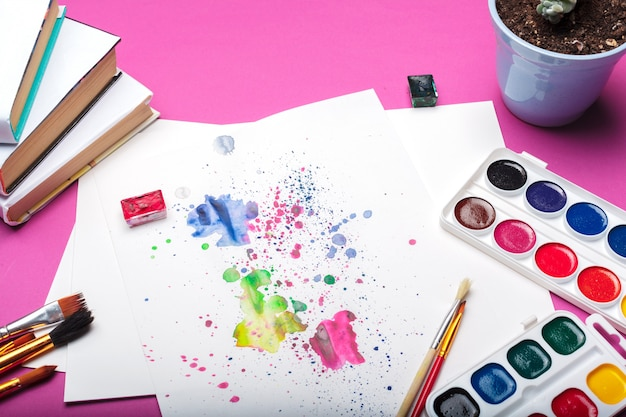 Vue de dessus de fournitures de peinture aquarelle, pinceaux et crayon coloré.