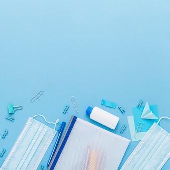 Vue de dessus des fournitures scolaires avec copie espace et masques