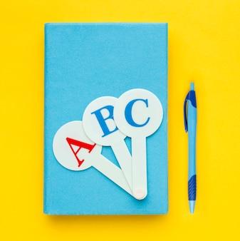 Vue de dessus des fournitures scolaires avec un crayon et un livre