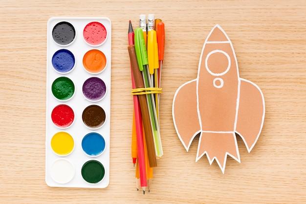 Vue de dessus des fournitures scolaires avec crayons et aquarelle