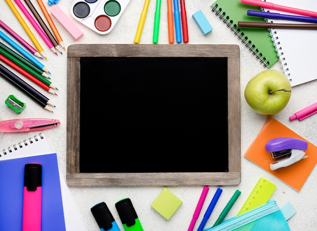 Vue de dessus des fournitures scolaires avec des crayons colorés et un tableau noir