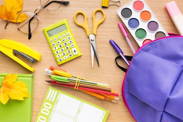 Vue de dessus des fournitures scolaires avec crayons et sac à dos