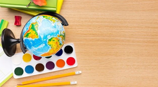 Vue de dessus des fournitures scolaires avec globe et espace copie