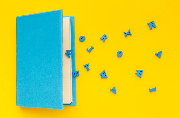 Vue de dessus des fournitures scolaires avec des lettres et un livre
