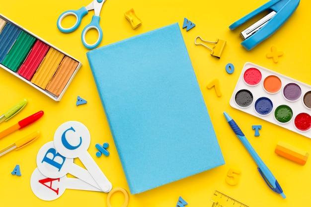 Vue de dessus des fournitures scolaires avec livre et aquarelle