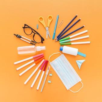 Vue de dessus des fournitures scolaires avec masque et crayons