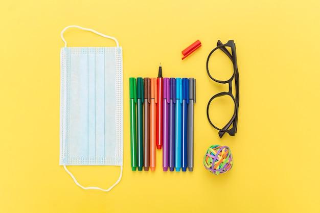Vue de dessus des fournitures scolaires avec masque et lunettes